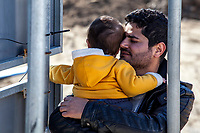 MYTILINI, GREECE - FEBRUARY 09: A man holds his young son while waiting for registration at the Moria refugee camp on February 09, 2015 in Mytilini, Greece. After travelling for more than two hours crossing the Aegean sea, refugees are picked up by buses run by UNHCR and transferred to the Moria refugee camp where they have to register their names. As thousands of refugees arrive everyday in Lesvos, queues for registration can take up to two days. In the camp several international organisations provide assistance to the refugees as food, medical assistance, blankets and clothes among other items and services. Photo: © Omar Havana. All Rights Are Reserved