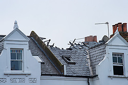 © Licensed to London News Pictures. 07/12/2020. London, UK. A severely damaged roof of the flat. Ten fire engines and around 70 firefighters responded a flat fire on Montserrat Road in Putney. Firefighters, using breathing apparatus rescued a man via an internal staircase from a second floor flat in a mid-terrace house of three floors. The man was treated for smoke inhalation by London Ambulance Service crews and taken to hospital. Photo credit: Peter Manning/LNP
