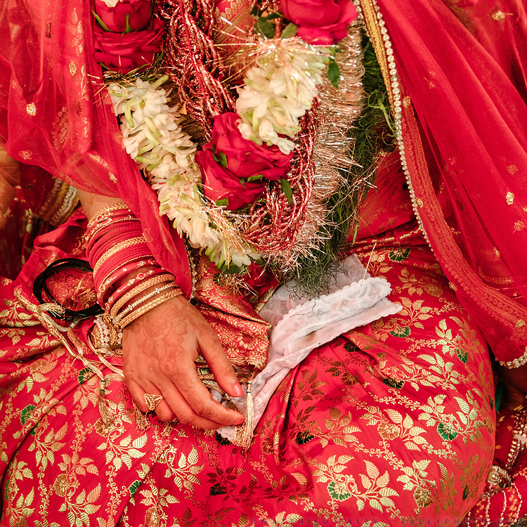 Details of the Bride's dress and hand during the last part of her wedding ceremony. This is the last day of a Hindu wedding that lasted 7 days. Soon, the Bride will leave her home.