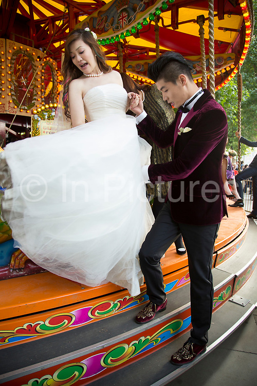Chinese wedding party of friends and relatives descend upon the South Bank, here riding as a group on the Marry-go-round. The happy couple who were from Beijing had only been in London for one day, having travelled to the UK just to get married.