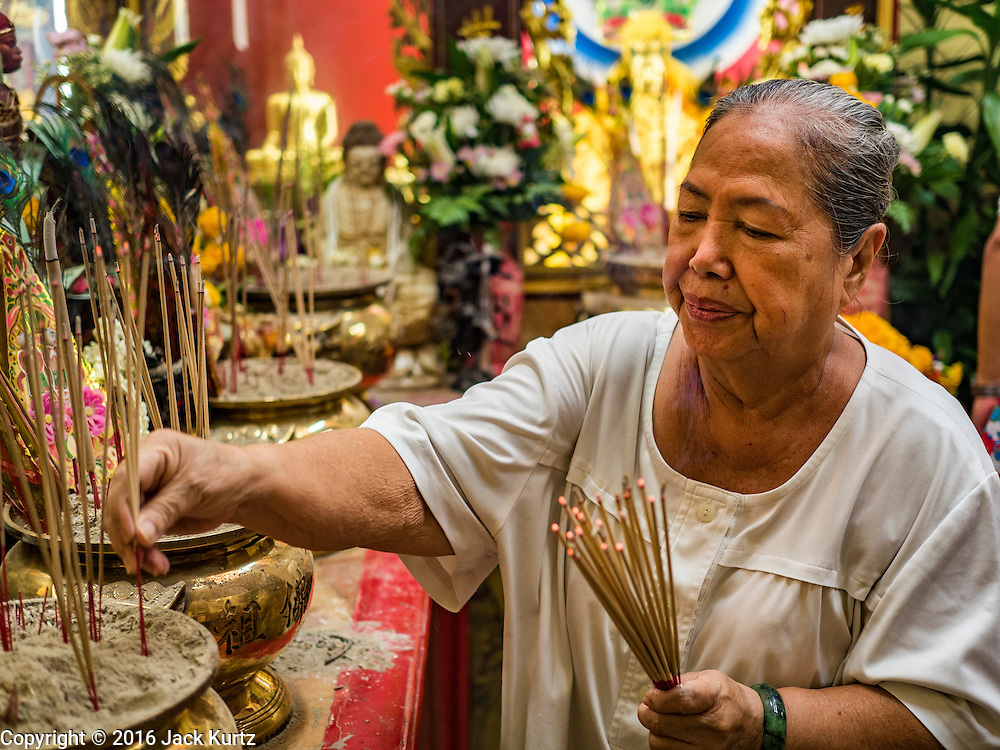 16 SEPTEMBER 2016 - BANGKOK, THAILAND: Women pray at Heng Chia Shrine on Chareon Krung Road during the Mid-Autumn Festival in Bangkok. The festival was originally a time to enjoy the successful reaping of rice and wheat and is still celebrated as a harvest festival in agricultural communities. In Bangkok, people make food offerings in honor of the moon. And it is an opportunity to share mooncakes.   PHOTO BY JACK KURTZ