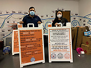 In Duluth, Georgia, Civic Engagement Coordinators Anthony Pacheco and Quynh Nguyen stand behind Election Protection signs. Voters can call Chinese, Hindi, Korean, Vietnamese and English language hotlines to have their voting questions answered.