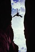 Doug Roe leaping over Peek-A-Boo Gulch slot canyon, Grand Staircase-Escalante National Monument, Utah.