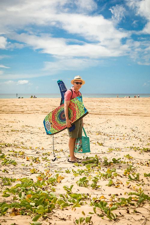 """""""When I go to the beach, I like to be prepared.""""  Alaskan Bart Simons walks toward the water in Hanapepe, Kauai, Hawaii."""