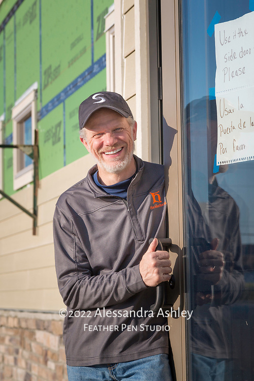 Business owner at front door of new physical therapy and wellness center building, with exterior work in progress.