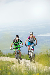 Mountain bikers cycling uphill in nature, Kampenwand, Bavaria, Germany