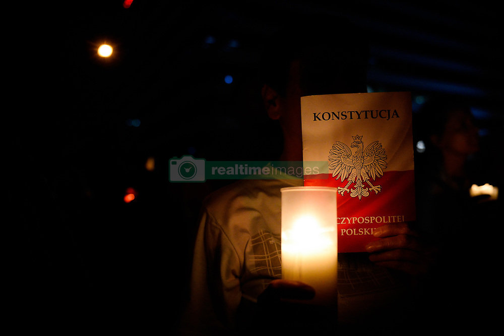 July 26, 2018 - Krakow, Poland - A woman seen holding a candle and a copy of the Polish Constitution during the demonstration..On the 7th day of a protest demanding free courts in front of Krakow court. The ruling Law and Justice (PiS) party adopted another round of amendments to the bills relating to the judiciary and now waits for the president's signature. (Credit Image: © Omar Marques/SOPA Images via ZUMA Wire)
