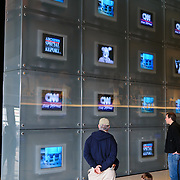 Visitors watch a wall of news broadcasts on TV screens. The Newseum is a 7-story, privately funded museum dedicated to journalism and news. It opened at its current location on Pennsylvania Avenue in April 2008.