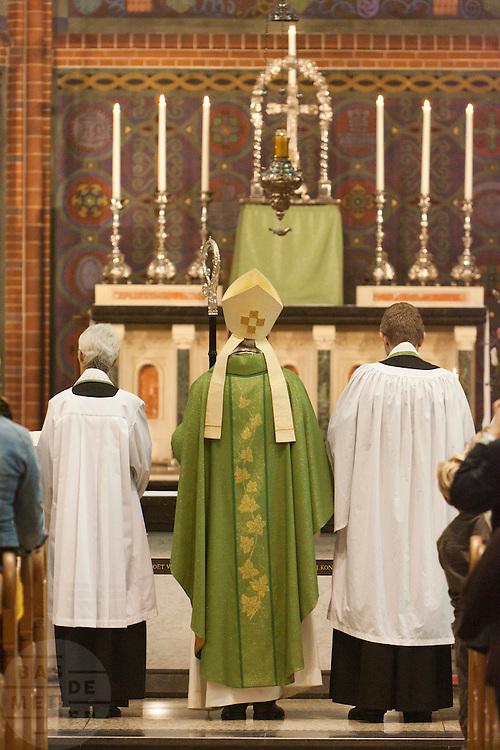 Aartsbisschop Joris Vercammen staat te midden van Annemieke Duurkoop (links) en Bernd Wallet voor het altaar. Op zondag 31 oktober is in de Getrudiskathedraal in Utrecht  Annemieke Duurkoop als eerste vrouwelijke plebaan van Nederland geïnstalleerd. Duurkoop wordt de nieuwe pastoor van de Utrechtse parochie van de Oud-Katholieke Kerk (OKK), deze kerk heeft geen band met het Vaticaan. Een plebaan is een pastoor van een kathedrale kerk, die eindverantwoordelijk is voor een parochie. Eerder waren bij de OKK al twee vrouwelijk priesters geïnstalleerd, maar die zijn geen plebaan.<br /> <br /> Archbishop Joris Vercammen is standing between the new dean Annemieke Duurkoop (left) and new pastor Bernd Wallet (right) for the altar. At the St Getrudiscathedral in Utrecht the first female dean of the Old-Catholic Church (OKK), Annemieke Duurkoop, is installed together with a new pastor Bernd Wallet. The church has no connections with the Vatican.