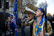 Anti Brexit pro Europe demonstrator with a megaphone shouts in protest waving European Union and Union Jack flags and placards in Westminster opposite Downing Street on the day the Prime Minister takes her draft Brexit deal to gain backing from her cabinet in Westminster on 14th November 2018 in London, England, United Kingdom.