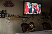 Suany, daughter of Irma, an asylum seeker from Honduras, sits at the dining room table of the family home as a news program showing U.S. President Donald Trump plays on the TV above her in Fort Worth, Texas, U.S., June 4, 2019. Suany and her family fled violence in Honduras to seek asylum in America, but now await a ruling on their case. The statistics say they are likely to eventually have their case rejected by an immigration judge, resulting in a deportation order to return to Honduras.