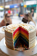 Rainbow coloured cake in a cafe window in London, United Kingdom.