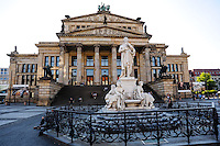 Berlin, Germany. The Gendarmenmarkt is a large and famous square in Berlin. The Konzerthaus Berlin is a concert hall, rebuilt and reopened in 1984. Friedrich Schiller statue in foreground.
