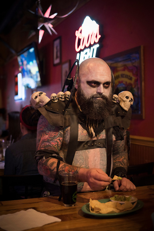 Johnson City, TN - October 29, 2016: Stephen Garland eats a chip at Holy Taco, a restaurant in downtown Johnson City, TN. He is dressed as a Mad Max character, one of many patrons in costume on this Halloween weekend.