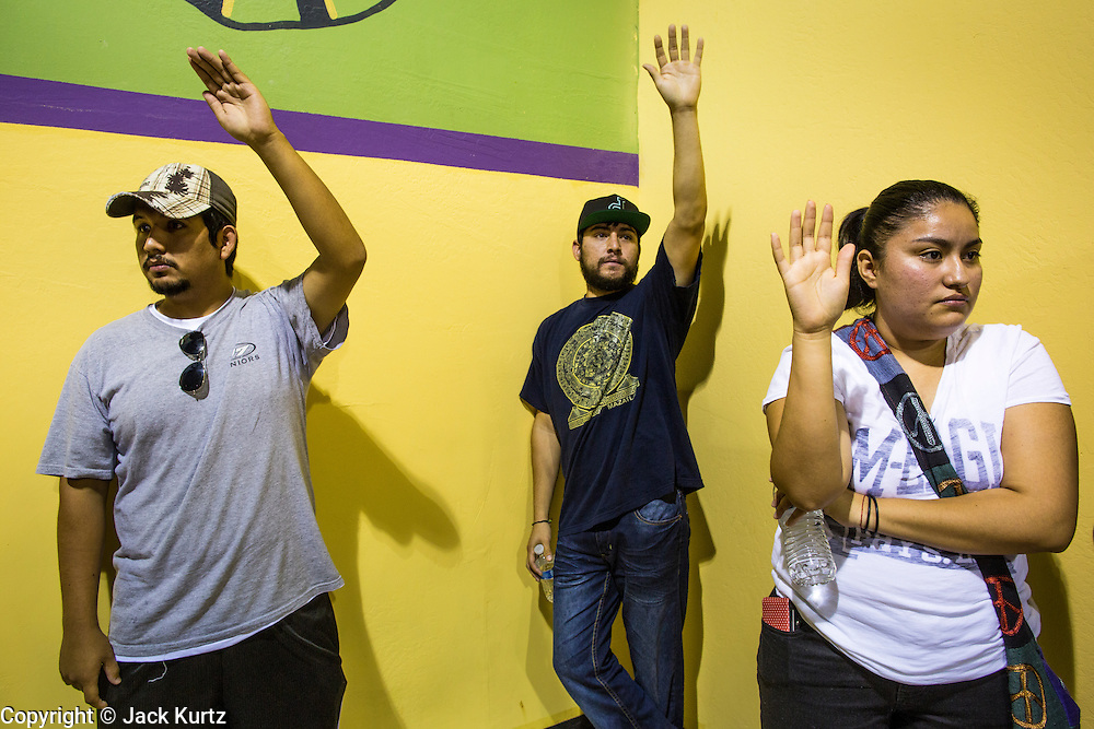 """18 AUGUST 2012 - PHOENIX, AZ:  People hold their hands up waiting to receive information packets at a deferred action workshop in Phoenix. More than 1000 people attended a series of 90 minute workshops in Phoenix Saturday on the """"deferred action"""" announced by President Obama in June. Under the plan, young people brought to the US without papers, would under certain circumstances, not be subject to deportation. The plan mirrors some aspects the DREAM Act (acronym for Development, Relief, and Education for Alien Minors), that immigration advocates have sought for years. The workshops were sponsored by No DREAM Deferred Coalition.  PHOTO BY JACK KURTZ"""