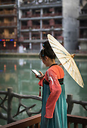 Side view waist up shot of a woman in a traditional Chinese dress and with an umbrella using a smartphone, Fenghuang, Hunan Province, China