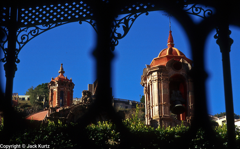 16 JANUARY 2002, GUANAJUATO, GUANAJUATO, MEXICO: The bell tower and steeple of Templo San Diego, a historic Catholic church, is framed by wrought iron grill work in the gazebo of Plaza Union Jardin in the city of Gunajuato, state of Guanajuato, Mexico, Jan. 16, 2002.  .PHOTO BY JACK KURTZ