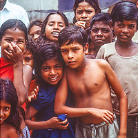 Youngsters giggle to watch a family planning discussion at Mirpur Destitute Camp near Dhaka, Bangladesh.  1977