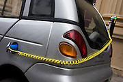 A power cable plugs into the place of a petrol cap while recharging G-Wiz car in central London.