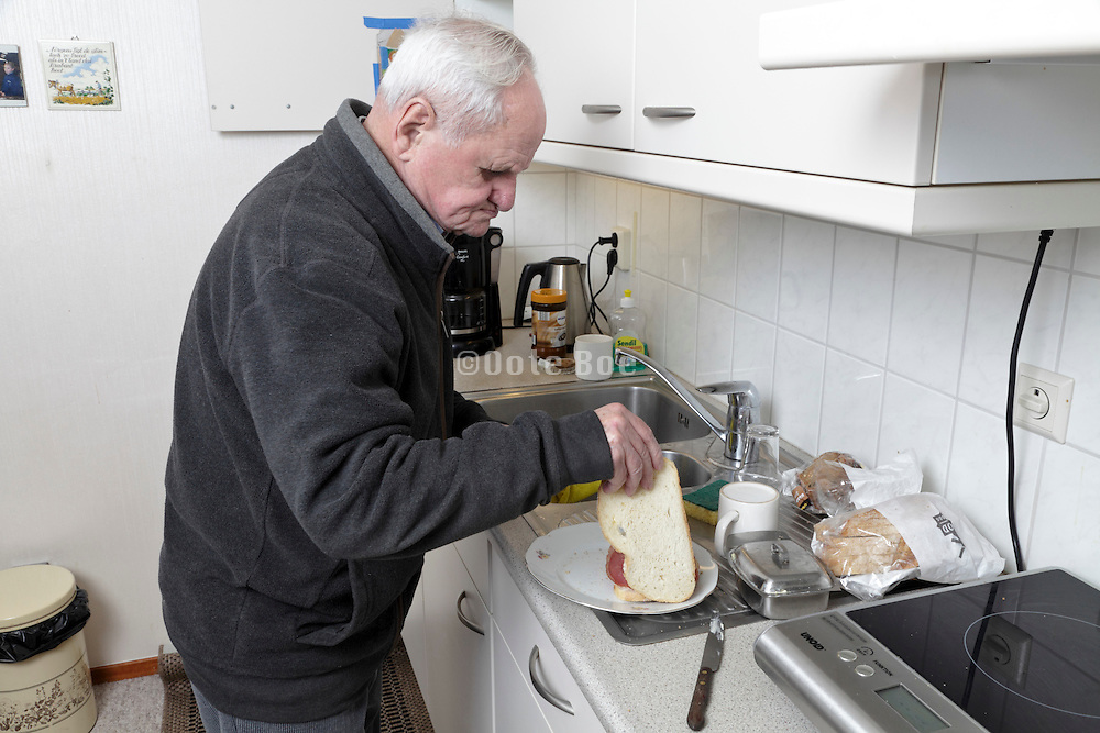 senior 89 year old man making a sandwich