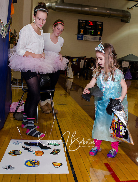 """Jillian Barton and Haleigh Patch help """"Frozen Fever"""" Hayley Merriam in the Bat Toss game at Gilford Middle School's Halloween Party Friday evening.   (Karen Bobotas/for the Laconia Daily Sun)"""