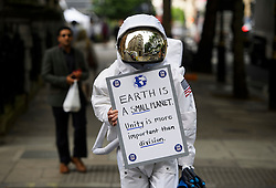 © Licensed to London News Pictures. 21/06/2016. London, UK. A man dressed as a space man holds up a placard campaigning for a remain vote, in Westminster, central London, ahead of a referendum on the UK's membership of the EU on June 23rd.. Photo credit: Ben Cawthra/LNP