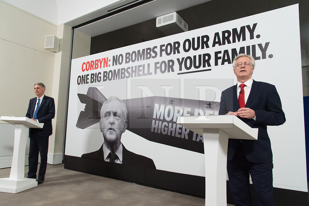 """© Licensed to London News Pictures. 03/05/2017. London, UK. Chancellor of the Exchequer PHILLIP HAMMOND and DAVID DAVIES the Secretary of State for Exiting the European Union speak at a General Election Campaign event featuring a poster of Labour party leader JEREMY CORBYN with the slogan """"More debt, higher tax."""" Photo credit: Ray Tang/LNP"""