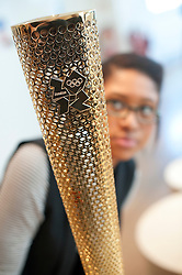 © Licensed to London News Pictures. 07/02/2012. A Design Museum worker poses next to The London 2012 Olympic Torch by Edward Barber and Jay Osgerby on display at  Design of the Year  2012, at the Design Museum in London on February 7th, 2012. The awards showcase the most innovative designs from around the world, covering seven categories: architecture, fashion, furniture, graphics, interactive, product and transport. Photo credit : Ben Cawthra/LNP