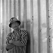 Portrait of a vietnamese worker after shift, outside a rice farming cooperative that process drying and packing up operations. Can Tho region, Mekong delta, Vietnam.2005.
