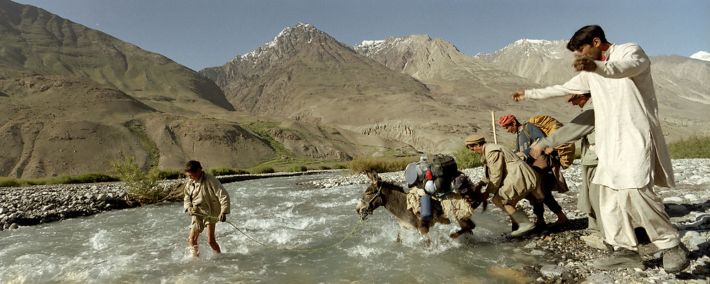 After a night spent with some Pakistani Wakhi friends from Chapursan valley, we head on further into the Wakhan Corridor. Our donkey is very shy with waters, which worries us a bit... Ashur Baig leads him across turbulent water.<br /> <br /> Adventure through the Afghan Pamir mountains, among the Afghan Kyrgyz and into Pakistan's Karakoram mountains. July/August 2005. Afghanistan / Pakistan.