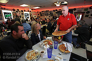 Charlie Parker's Diner owner, Mike Murphy, shows patrons giant pancake which earn challengers a free meal if they can eat four in one sitting; Springfield, Illinois.