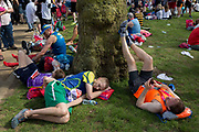 Tired long-distance runners rest after finishing the London Marathon, in St Jamess Park, on 22nd April 2018, in London, England.
