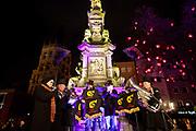 A choir sing carols on a statue at the Christmas market Markt der Engel / Angel Market on Neumarkt, Cologne.