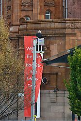 © Licensed to London News Pictures. 03/10/2012. Manchester, UK A man removes a banner welcoming the conference on Day 5 at The Labour Party Conference at Manchester Central today 3rd october 2012. Photo credit : Stephen Simpson/LNP