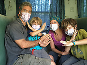 Family travelling in a train, wearing face mask.