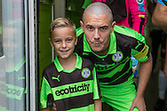 Forest Green Rovers Liam Noble (15) with mascot Olly during the Vanarama National League match between Forest Green Rovers and Bromley FC at the New Lawn, Forest Green, United Kingdom on 17 September 2016. Photo by Shane Healey.
