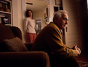 A woman stands in a doorway looking at her father sitting in a chair