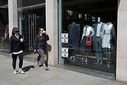 As the UK's Coronavirus death toll during the government's social distancing lockdown, rose by 384 to 33,998, and the R rate of infection is reported to be between 0.7 and 1.0, two women walk past clothing mannequins in the window of a closed branch of Ted Baker, are covered in polythene plastic, in the City of London, the capital's now empty financial district, on 15th May 2020, in London, England.