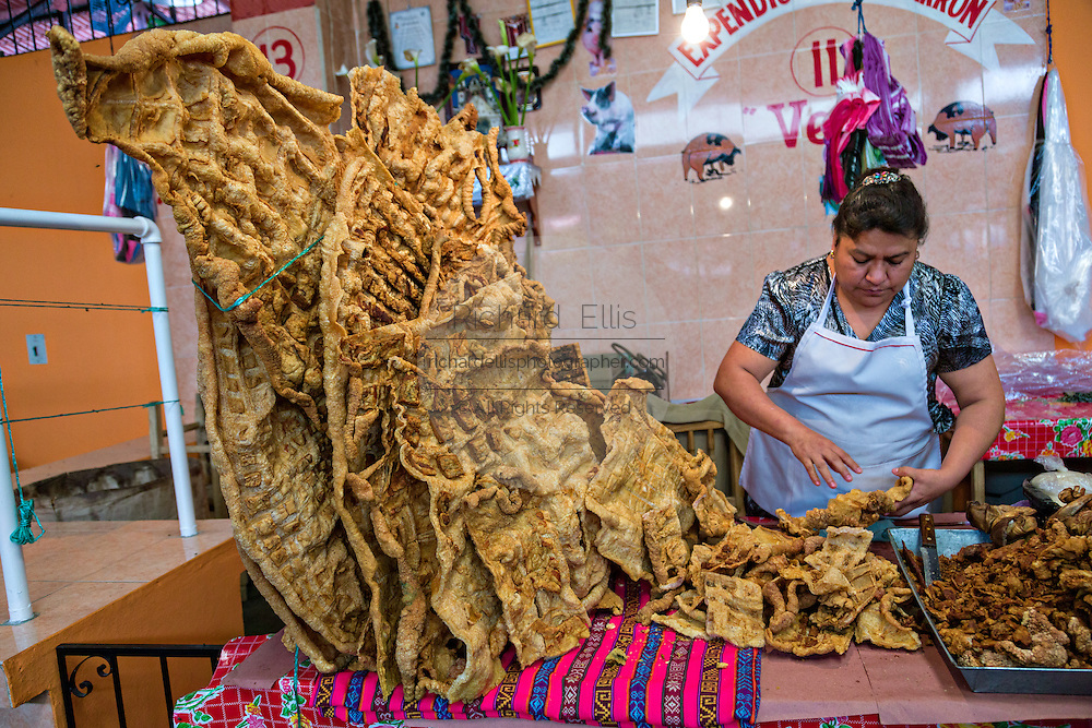 A woman selling fried pig skin at the Sunday market in Tlacolula de Matamoros, Mexico. The regional street market draws thousands of sellers and shoppers from throughout the Valles Centrales de Oaxaca.