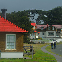 Visitors walk past the lighthouse keepers' houses at Point Cabrillo Light Station, near Pine Grove, California.