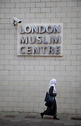 Woman wearing a head scarf passes the London Muslim Centre under a CCTV surveillance camera on Whitechapel High Street in East London. This area in the Tower Hamlets is predominantly Muslim with just over 50% from Bangladeshi descent. This is known as a very poor area of London's East End.
