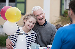 Grandfather hugging his granddaughter on her birthday party and smiling, Bavaria, Germany