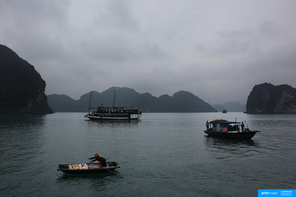 A local seller rows to tourist boats to sell her goods in Ha Long Bay, Vietnam. The bay consists of a dense cluster of 1,969 limestone monolithic islands. Ha Long Bay, is a UNESCO World Heritage Site, and a popular tourist destination. Ha Long, Bay, Vietnam. 11th March 2012. Photo Tim Clayton