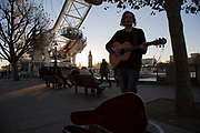 Musician Conor Scott busking with sun setting on the Southbank riverside walkway, London, United Kingdom. The South Bank is a significant arts and entertainment district, and home to an endless list of activities for Londoners, visitors and tourists alike. (photo by Mike Kemp/In Pictures via Getty Images)