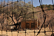 An abandoned gold mine camp cabin constructed from rock sits along a creek in the Santa Rita Mountains, Coronado National Forest, Sonoran Desert, Sonoita, Arizona, USA.