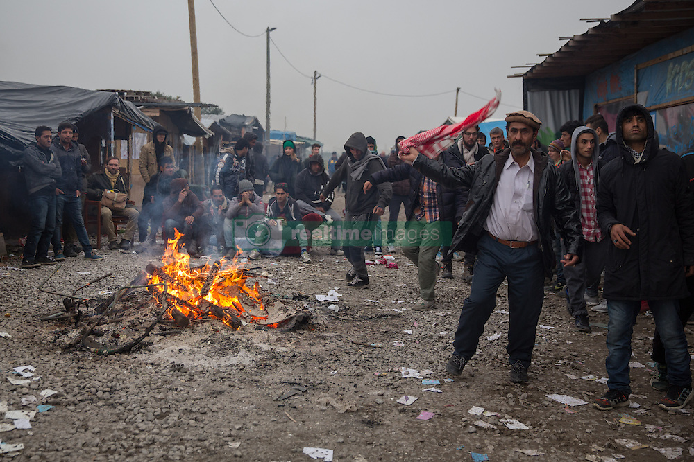 """Dschungel von Calais: Das wilde Fl¸chtlingslager wird ger‰umt und die Fl¸chtlinge in Aufnahmezentren verteilt / 241016 *** Calais, Pas-de-Calais, France - 24.10.2016    <br />  <br /> Refugees dance arround a fire. Start of the eviction on the so called îJungle"""" refugee camp on the outskirts of the French city of Calais. Refugees and migrants leaving the camp to get with buses to asylum facilities in the entire country. Many thousands of migrants and refugees are waiting in some cases for years in the port city in the hope of being able to cross the English Channel to Britain. French authorities announced a week ago that they will evict the camp where currently up to up to 10,000 people live.<br /> <br /> Fluechtlinge tanzen um ein Feuer herum. Beginn der Raeumung des so genannte îJungleî-Fluechtlingscamp in der franzˆsischen Hafenstadt Calais. Fluechtlinge und Migranten verlassen das Camp um mit Bussen zu unterschiedlichen Asyleinrichtungen gebracht zu werden. Viele tausend Migranten und Fluechtlinge harren teilweise seit Jahren in der Hafenstadt aus in der Hoffnung den Aermelkanal nach Groflbritannien ueberqueren zu koennen. Die franzoesischen Behoerden kuendigten vor einigen Wochen an, dass sie das Camp, indem derzeit bis zu bis zu 10.000 Menschen leben raeumen werden. <br /> <br /> Photo: Bjoern Kietzmann"""