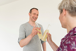 Mature couple toasting drink bottle, smiling