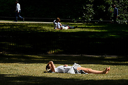 © Licensed to London News Pictures. 16/07/2019. LONDON, UK.  A woman relaxes in the sunshine in St. James's Park.  Temperatures are forecast to rise to 26C.  Photo credit: Stephen Chung/LNP