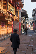View of pedestrians and old houses along a street in an old Chinese town, Fenghuang, Hunan Province, China