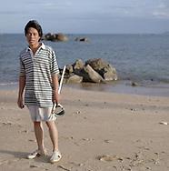 Young Vietnamese man stands on My Khe Beach with fishing gear, Da Nang, Vietnam, Southeast Asia